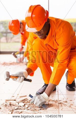 builders removing old floor tiles using a hammer and chisel poster