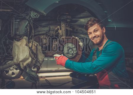Mechanic checking car brake system in a workshop