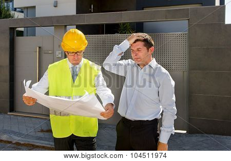 Desperate Customer In Stress And Constructor Foreman Worker With Helmet And Vest Arguing Outdoors