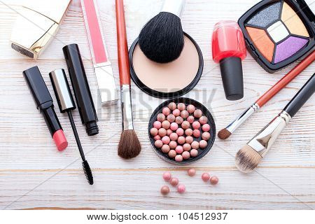 Makeup cosmetics products on white wooden background with copy space. Cosmetics make up artist objects: lipstick, eye shadows, eyeliner, concealer, nail polish, powder, tools for make-up. Selective focus poster