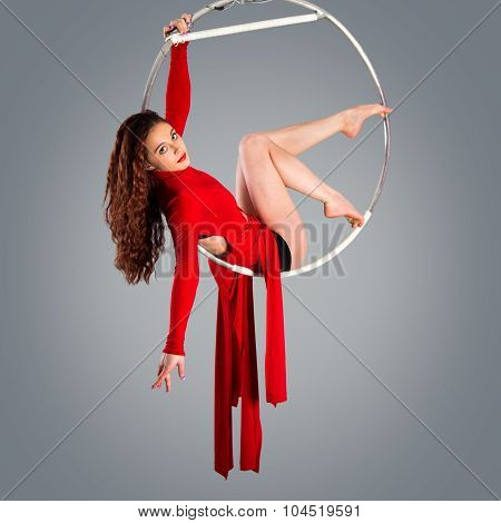 Plastic beautiful girl gymnast on acrobatic circus ring in flesh-colored suit. Aerial ring. poster
