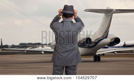 Business man holding on to his hat at the airport