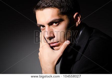 Young businessman in dark studio