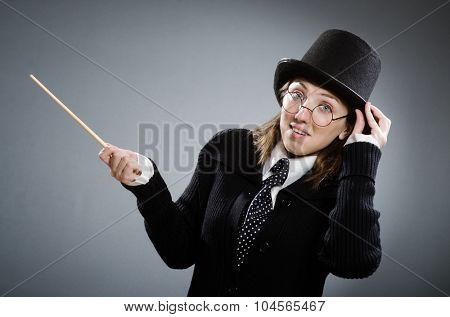 Harry Potter girl with magic stick against gray