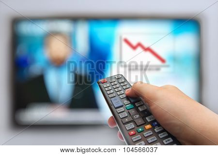Remote control in hand and TV.