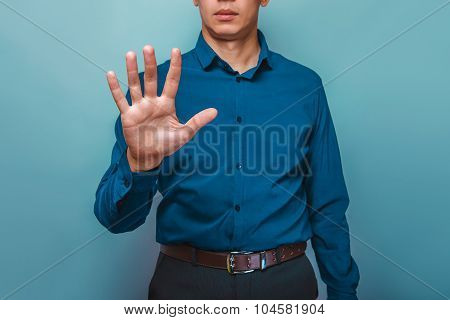 a man can be seen half-face shows the 5 fingers hand on a gray b