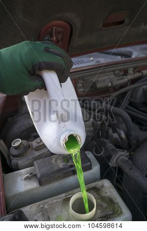 Mechanic Filling Vehicle With New Antifreeze