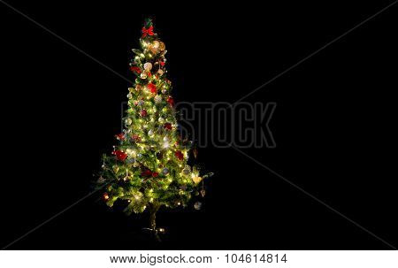 winter, holidays, decoration and illumination concept - beautiful decorated and illuminated christmas tree over black background