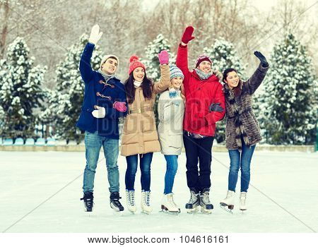 people, winter, friendship, sport and leisure concept - happy friends ice skating and waving hands on rink outdoors poster