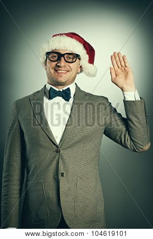 Confident nerd in Santa Claus hat and bow tie celebrates Christmas