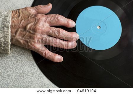 Senile hand is on vinyl LP. Close-up of the old woman hand. Space for your text.