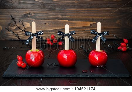 Three red caramel apples. Traditional dessert recipe for Halloween party. Selective focus.