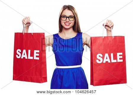 Pretty girl in blue dress and eyeglasses holding paperbags announcing sale