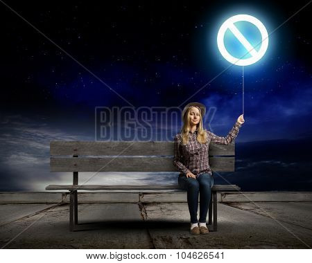 Young woman in casual holding balloon with prohibition sign poster