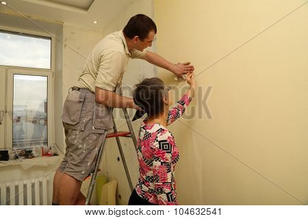 Woman customer and the worker putting up wallpaper