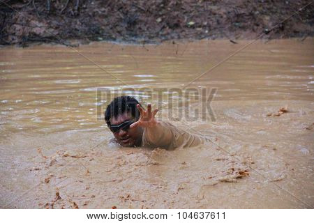 MUSKOGEE, OK - Sept. 12: An actor pretending to be a zombie plays in mud, while waiting for runners during the Castle Zombie Run at the Castle of Muskogee in Muskogee, OK on September 12, 2015.
