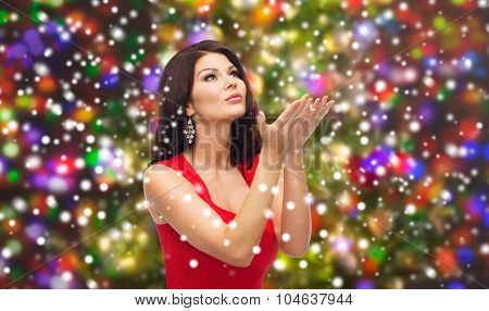 people, holidays, christmas, magic and fashion concept - beautiful sexy woman in red dress sending blow kiss or making wish over lights background