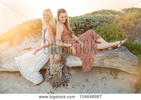Two girl friends laughing together outside at the beach