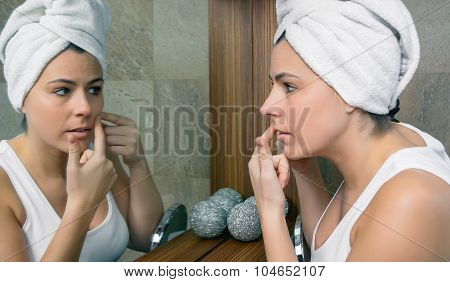Young woman squeezing an acne pimple in mirror
