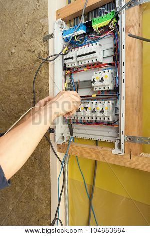 Hand of an electrician with screwdriver at an electrical switchgear cabinet