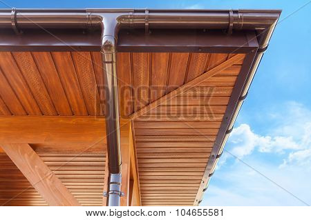 Brown copper gutter under a cloudy blue sky