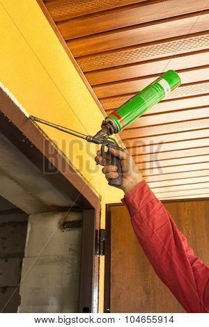 Construction builder works with polyurethane foam during frame insulation at door installation