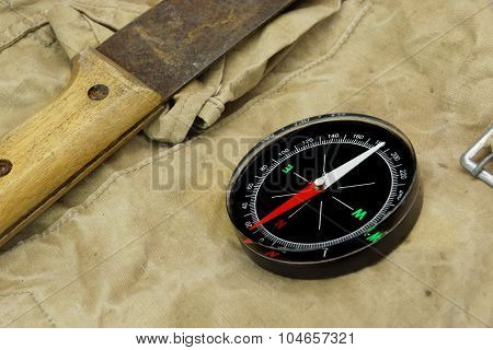 Machete And Magnetic Compass On The Weathered Backpack Background poster