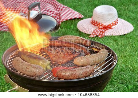 Close-up Of Bbq Grill And Picnic Blanket In The Background