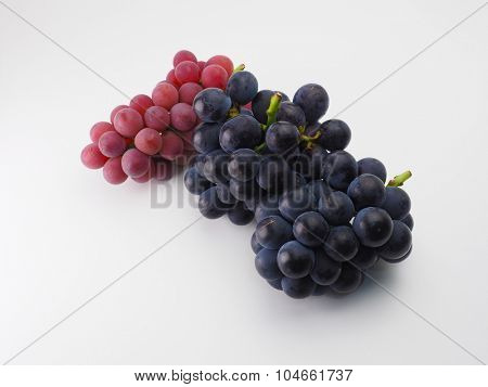 Plump Kyoho grapes (giant mountain grapes) and red grapes on natural white background.