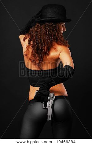 Rear View Of Sexy Gangster Hiding A Handgun.