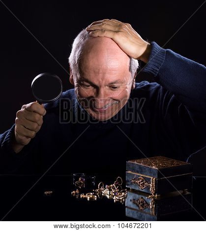 Senior jeweler looking at jewelry on a dark background poster