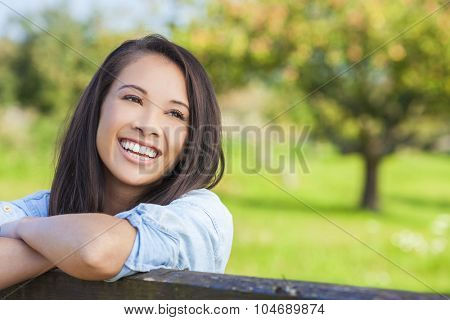 Beautiful happy Asian Eurasian young woman or girl wearing denim shirt, smiling with perfect teeth and leaning on fence in sunshine
