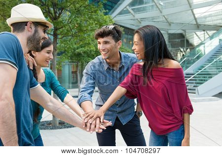 Closeup shot of young friends making huddle with their hand. Happy smiling friends. Happy young friends making huddle. Portrait of a group of people with their hands stacked in a city center.