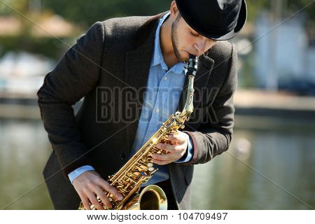 Young man playing on saxophone on the riverside poster