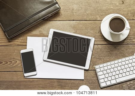 blank phone and tablet device placed over empty white paper sheets on a wooden workspace