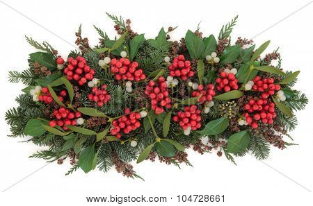 Christmas holly and mistletoe floral display with winter greenery of blue spruce and cedar cypress leyland over white background.