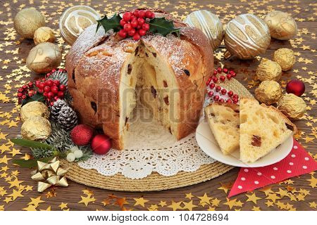 Panettone christmas cake and slice with bauble decorations, holly and winter flora over oak background with stars. poster