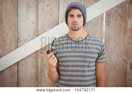 Portrait of hipster holding smoking pipe while standing against wooden wall