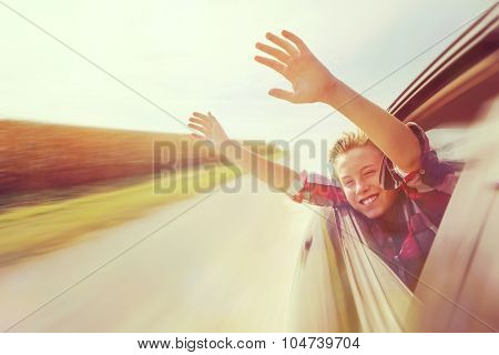 Boy putting his heads and hands out of the car window driving down a country road. Instagram effect.