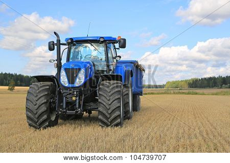 New Holland Tractor And Agricultural Trailer On Field In Autumn