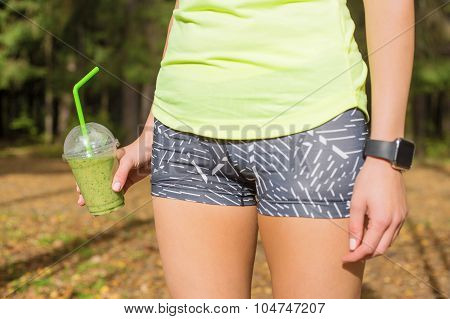 Woman standing  with green smoothie in her hand