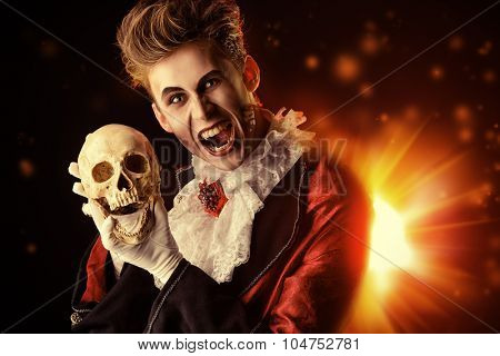 Horrible bloodthirsty vampire holding a skull. Halloween. Dracula costume.