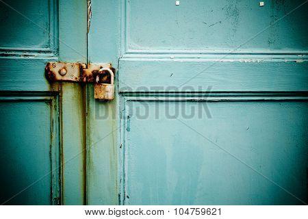 Rusty Padlock On Old Blue Painted Wooden Door