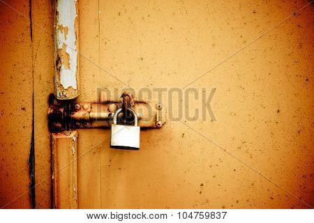 Rusty Padlock On Old Orange Painted Wooden Door