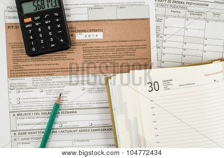 Polish tax form with pencil, calendar and calculator