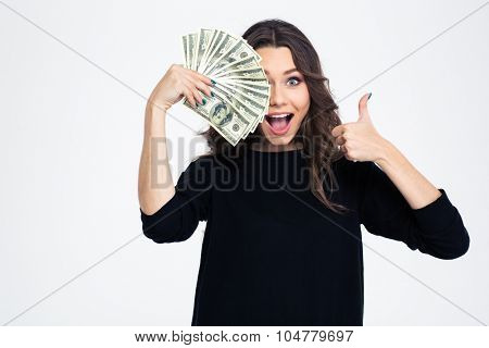 Portrait of a cheerful girl covering her eye with dollar bills and showing thumb up isolated on a white background