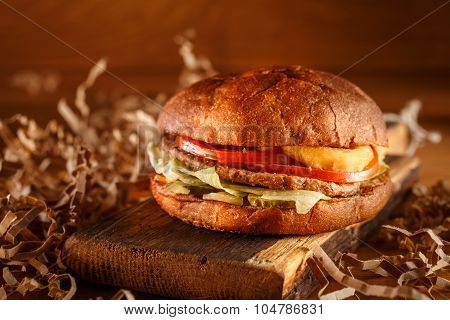 Burger on cutting board on vintage style. Homemade burger or hamburger in dramatic light. Vintage burger or hamburger on old wooden background. Homemade fast food concept. Mouthwatering home made burger. Delicious burger. Rustic burger.