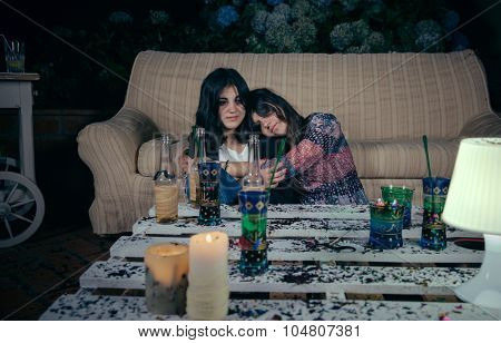 Young drunk woman sleeping embraced to her female friend sitting in the floor after outdoors party. Fun and alcohol and drugs problems concept. poster