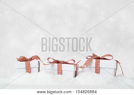 White Christmas Gift Boxes In Snow With Bokeh Background