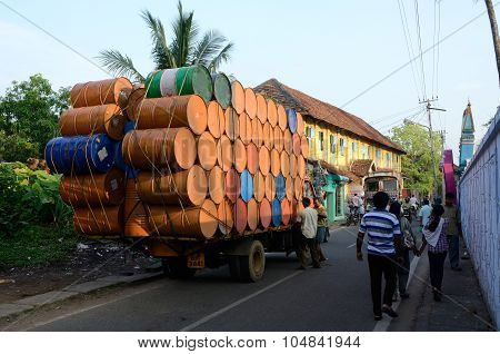indian drivers preparing heavily overloaded truck for travelling at Kerala state